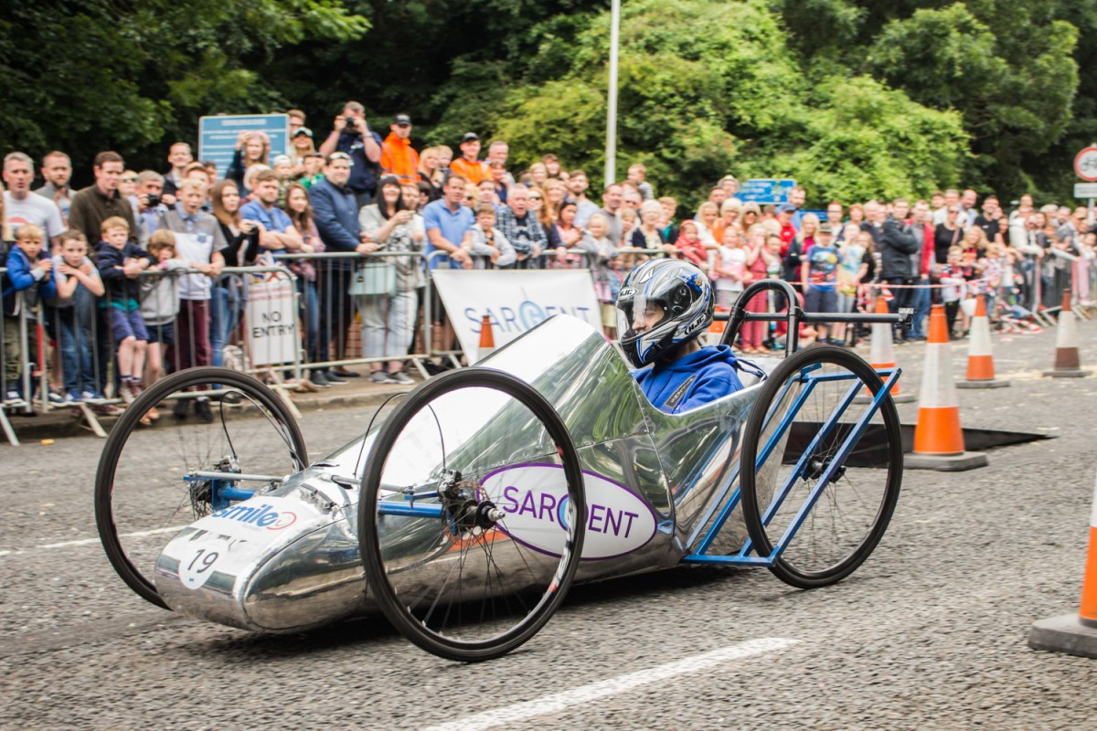 Sargent Electrical Soapbox going down a hill. Silver cart with big bike wheels.