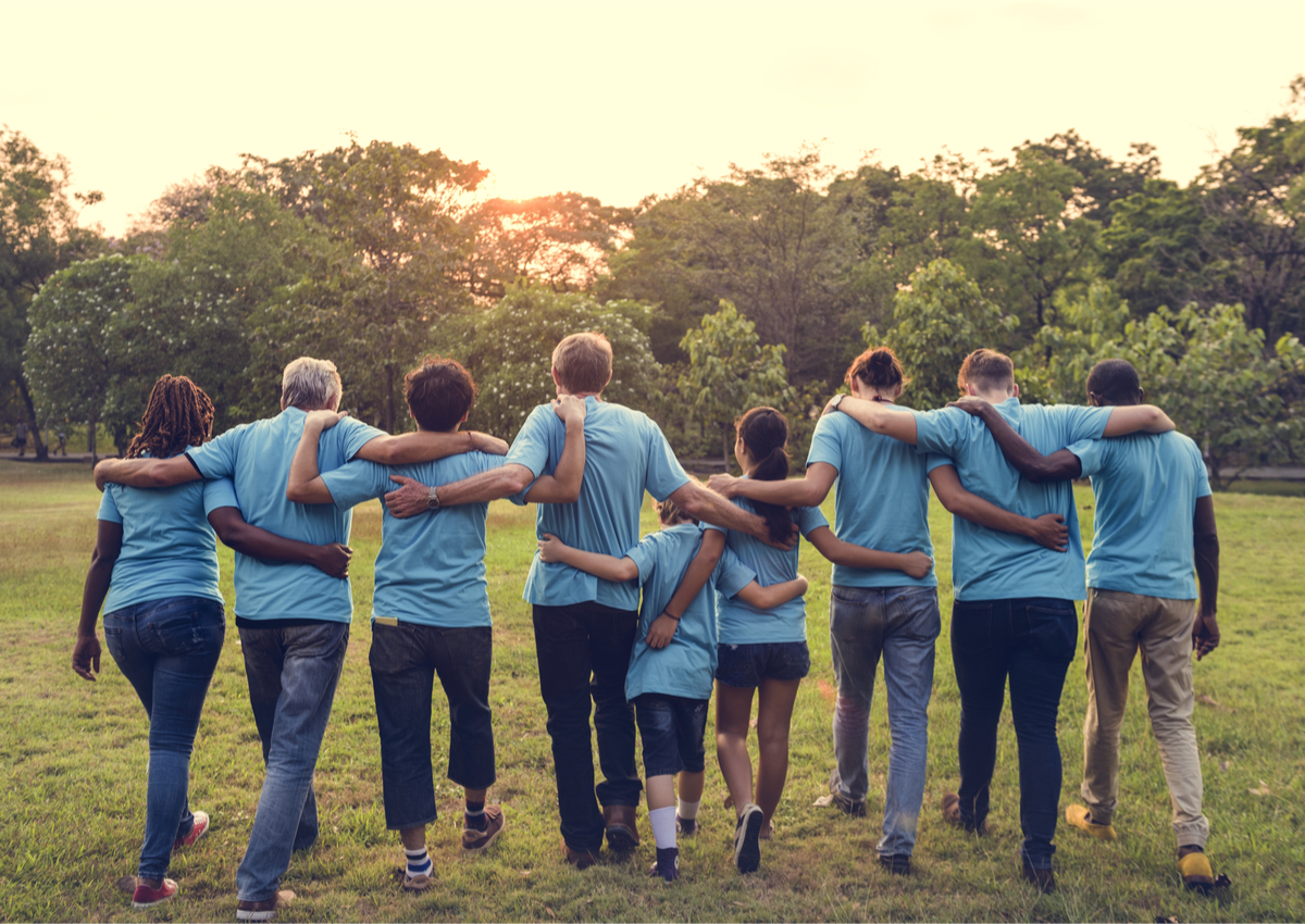 Seven volunteers of varying ages with their arms around each other walking away into the sunset