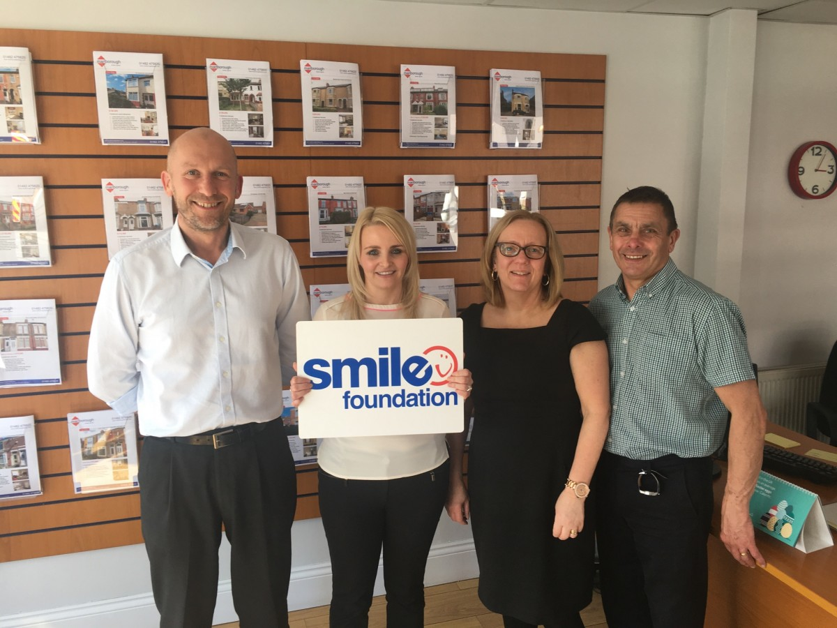 Marlborough Property Team holding Smile Foundation sign