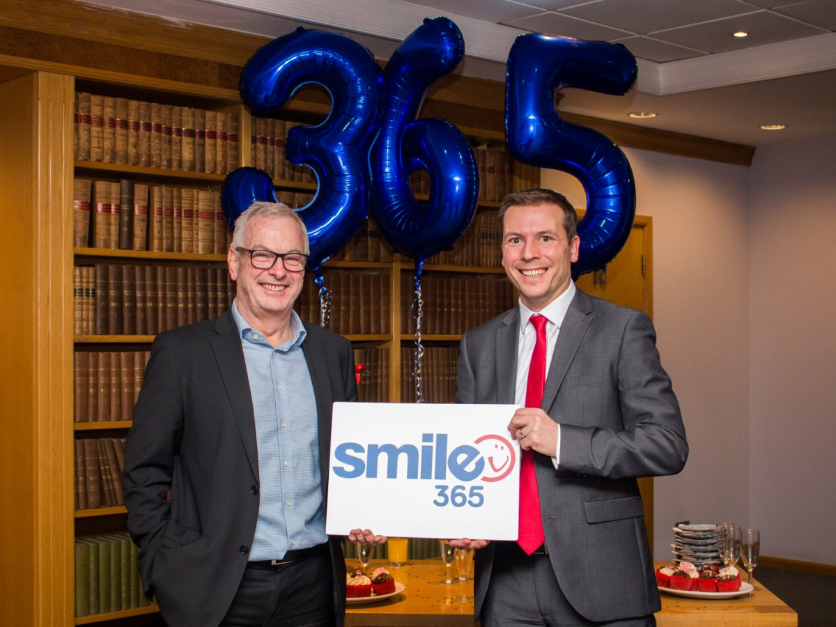 Mark Sharpley and Steve Bramall (Smailes Goldie) holding Smile365 sign with balloons in the background