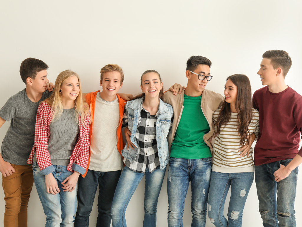Group of teenagers against a white wall